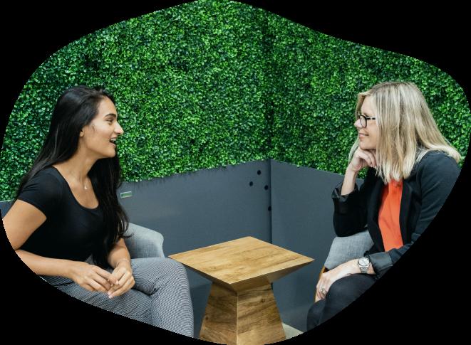 Two women talking in a lush office space