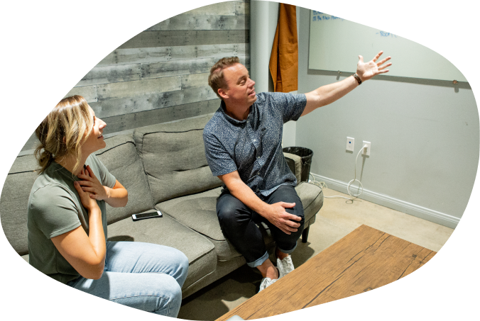 A TMYD coach gesturing at a whiteboard with an excited client next to them